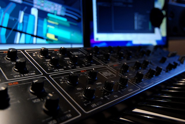 A Yamaha CS-15 in the studio, as the virtual world of the game looms in the background.