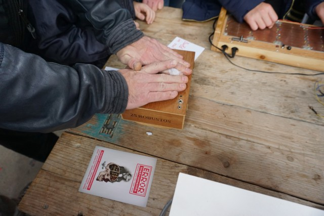 Visitors playing with a cracklebox